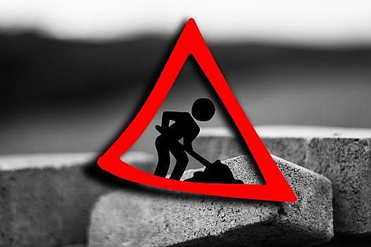 czerwony trójkąt z sylwetką pracującej z łopatą, w tle zbliżenie na kostkę brukową